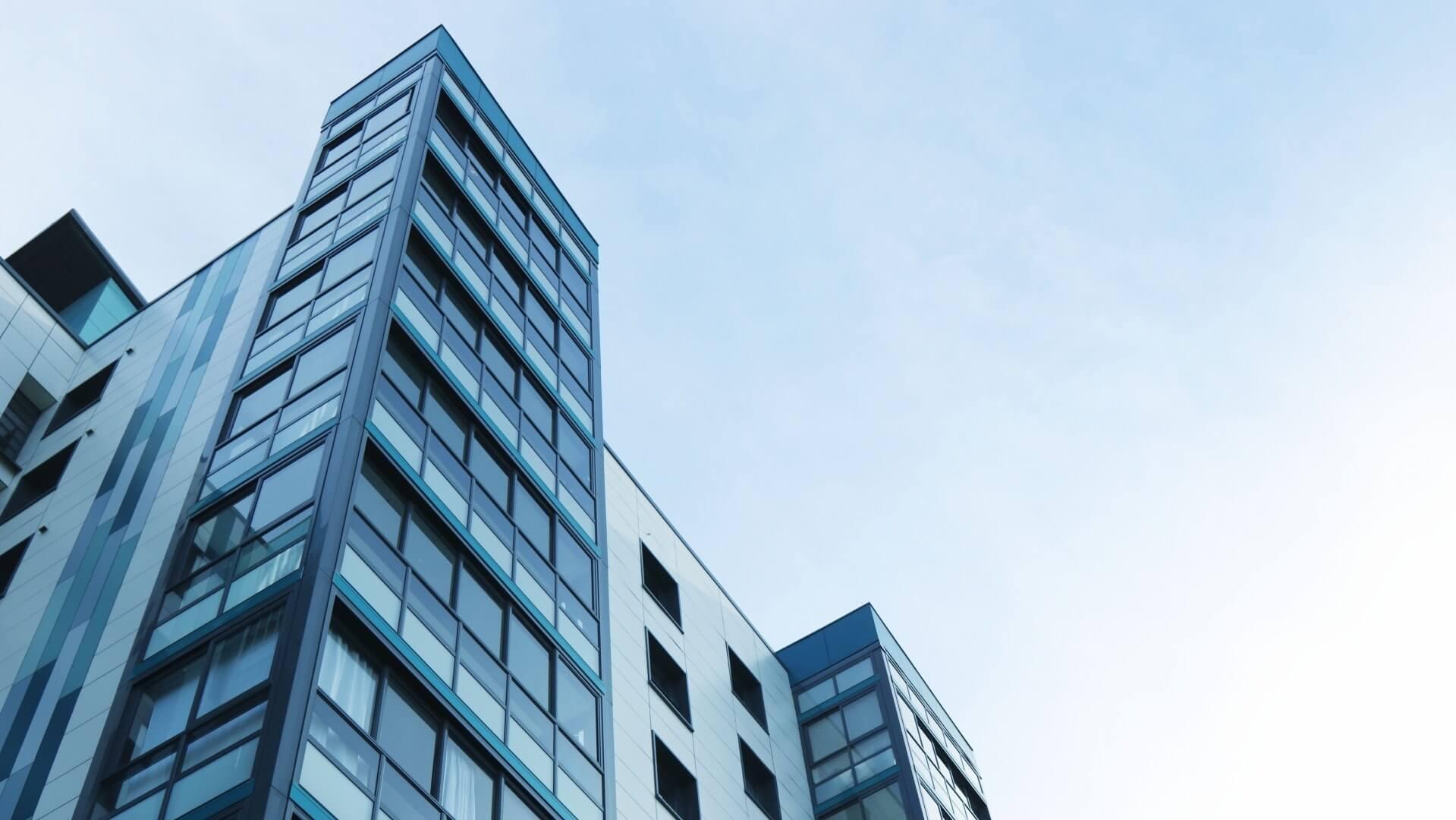 Ein blaugrauer Wolkenkratzer vor blauem Himmel